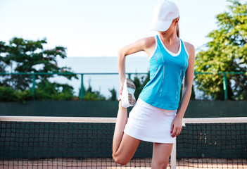 Portrait of a sports woman stretching leg outdoors