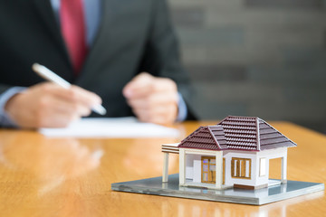 Businessman signing a contract to loan real estate