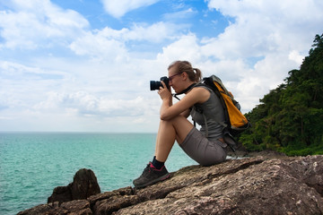 Young beautiful hiker photographer woman is sitting on rock and looking at sea through objective of her camera