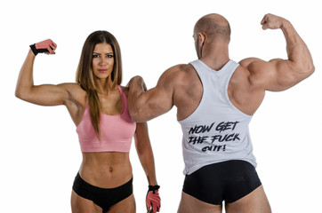 Young fitness couple posing with the muscles in front of the cam