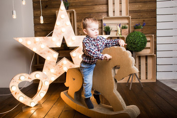 a boy sitting on a wooden horse inside a decorated wooden house