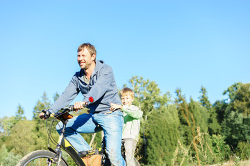 Happy family concept. Father and son riding on the bicycle in nature.