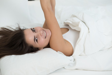 Woman lying in bed and stretching arms in the morning