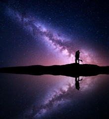 Milky Way. Night landscape with silhouettes of hugging and kissing man and woman on the mountain near the river with sky reflection in water. Starry sky. Lovers. Couple. Purple milky way with people
