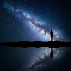 Milky Way. Night starry sky and silhouette of a standing woman on the mountain near the lake with sky reflection in water. Landscape with blue Milky Way and woman. Galaxy, Universe. Space background