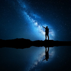 Milky Way. Silhouette of a standing man pointing finger in night starry sky on the mountain near the lake with sky reflection in water. Night landscape with universe. Blue milky way and man. Galaxy