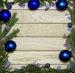New Year`s border frame from Christmas tree fir branches, silver pine cones, blue balls on vertical old wooden desk table background. Big copyspace for holiday congratulations.