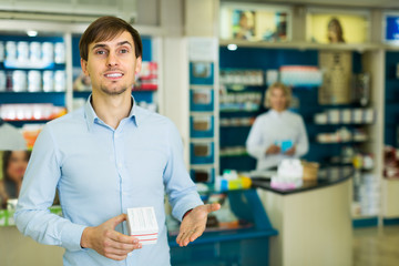 Man near counter in pharmacy