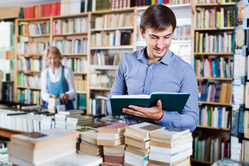 Young smiling man reading book while