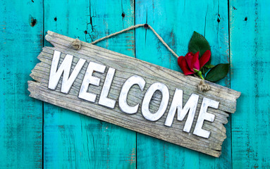 Welcome sign with single rose hanging on wood background