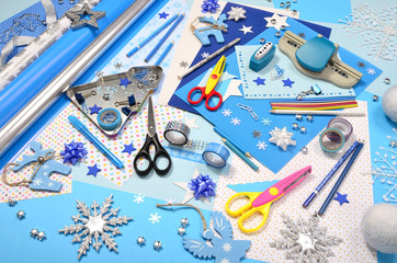 Arts and craft supplies for Christmas. Blue color paper, pencils, different washi tapes, craft scissors, wrapping paper rolls, festive Xmas supplies for decoration.