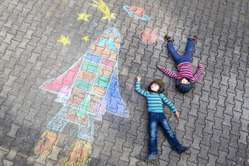 Two little kid boys flying by a space shuttle chalks picture