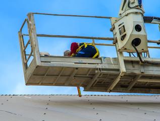 Worker repairs metal cover on a small passenger basket crane trucks