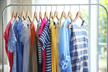 Wooden hangers with different female clothes in room
