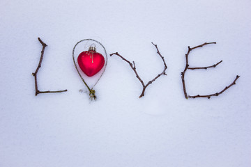 sign made of wood in the snow. St. Valentine's Day. red glass heart on snow
