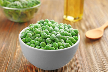 Frozen peas in bowl on wooden background