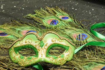 Exotic New Year or Mardi Gras image with peacock feathers and ornate feminine mask on a sparkly black fabric