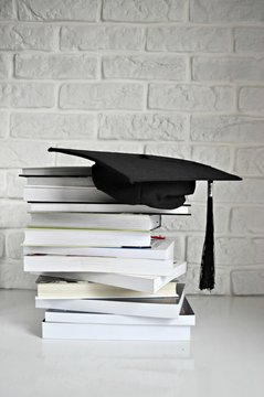graduation cap on the book on the desk; white background