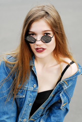 girl in a denim jacket and mirrored sunglasses looking at the ca