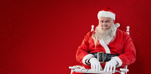 Composite image of santa claus typing on keyboard