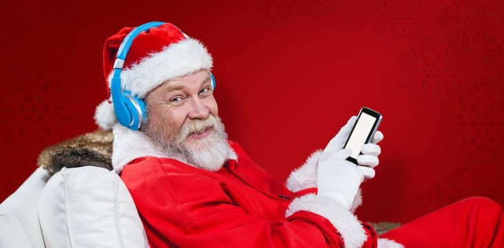 Composite image of santa claus with headphones using phone