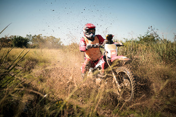 Off road dirt bike rider splashing mud in hard enduro rally race