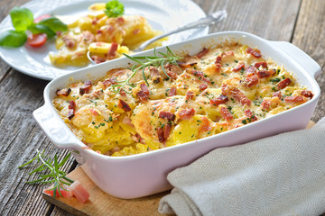 Kartoffelgratin mit Parmesan, Sahne und Südtiroler Speck frisch aus dem Ofen -  Potato gratin with parmesan cheese, cream and cured bacon from South Tyrol