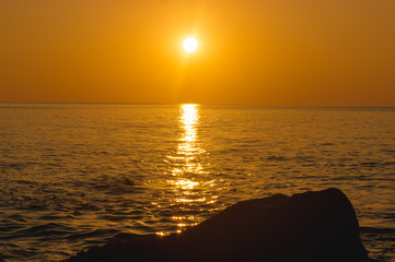 amazing tropical orange sunset over water, with rock silhouettes on Phuket Island, Thailand,