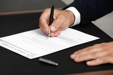 Man signing power of attorney, closeup