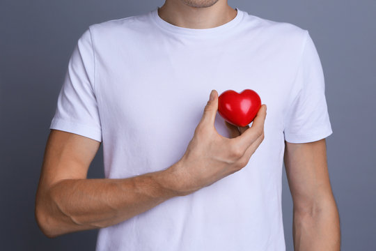 Young man holding red heart on color background