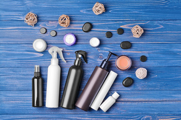 Different cosmetic bottles on blue wooden background