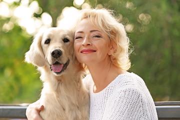 Senior woman sitting on bench with dog, closeup