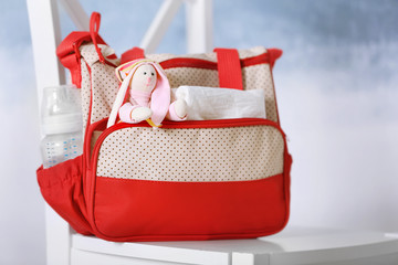 Mothers bag with toy and accessories on chair