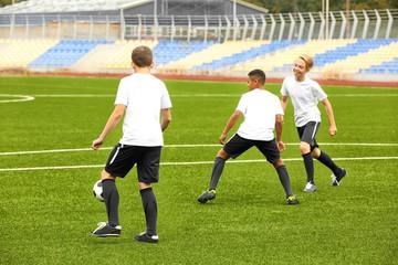 Boys playing football at stadium