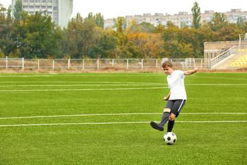 Boy playing football at stadium
