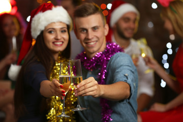 Young people with glasses of champagne at Christmas party, close up