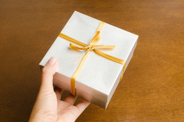 Silver gift box with golden ribbon holding by hand to giving in holiday