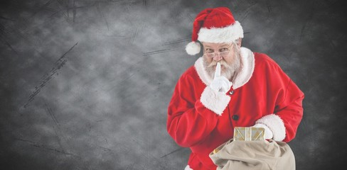 Composite image of santa claus with finger on lips and holding a