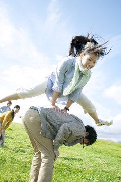 草原で馬跳びをする若者たち