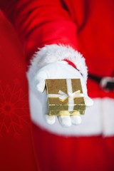 Composite image of santa claus holding gift box in hand