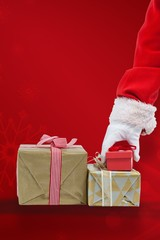Composite image of santa claus picking christmas gift