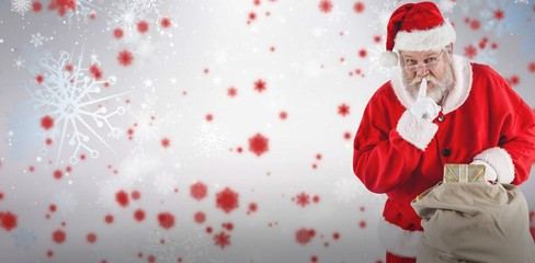 Composite image of santa claus with finger on lips and holding g