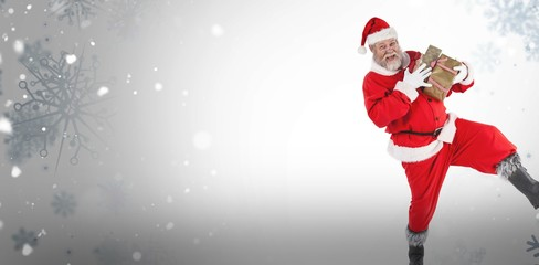 Composite image of portrait of playful santa claus holding prese