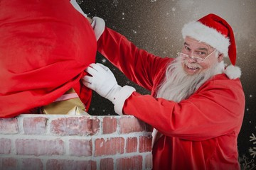 Composite image of santa claus placing gift box into chimney