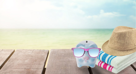 big sale travel piggy bank with sunglasses relax on the beach holiday. concept saving money for travel in holiday
