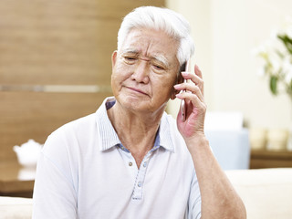 unhappy senior asian man talking on phone