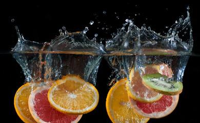 Orange, lemon, grapefruit and lime splashing into water