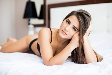 Gorgeous young woman posing seductively in her bedroom
