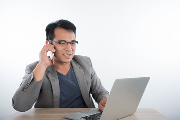 business man talking on a mobile phone and working on his laptop