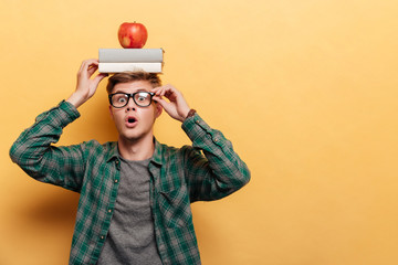 Astonished man student with book and apple on his head